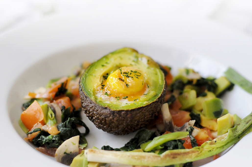 Boost Breakfast: Eggs Baked in Avocado with a side of Tomato, Spring Onions and Spinach